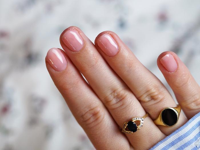 minimalistische goldene ringe mit schwarzen steinen sehr kurze nägel rosa nagellack nageldesign babyboomer blau weißes hemd