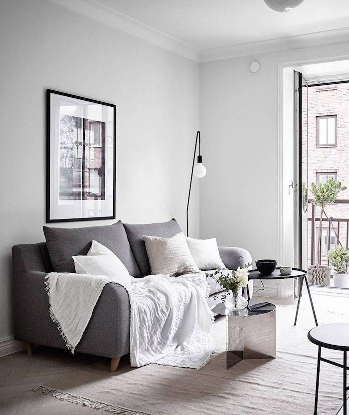 minimalistische inneneinrichtung interior design inspo wohnzimmer ideen modern großes schwarz weißes bild an die wand grauer couch weiße kissen und decke kaffeetisch schwarz