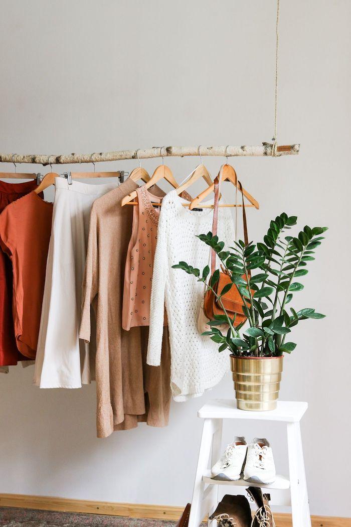 minimalistischer kleiderständer goldene vase grüne pflanze garderobe birkenstamm deko weiße sneaker aufgehängte klamotten wandfarbe weiß