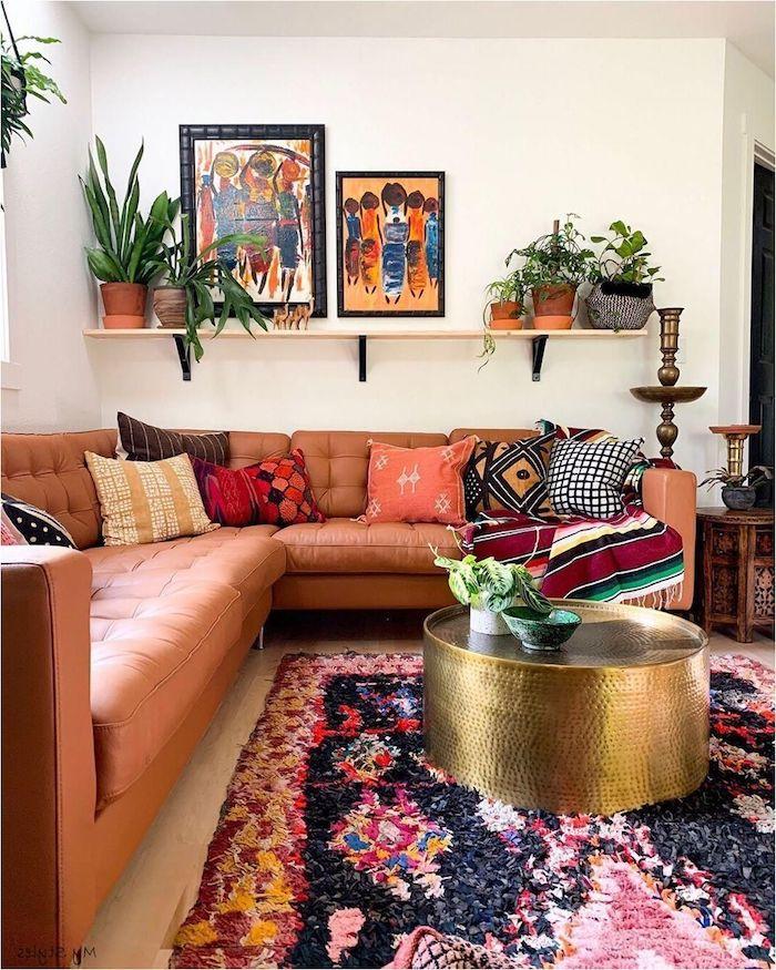 moderne dekoartikel stilvolle deko wohnzimmer modern einrichten boho chic inneneinrichtung ecksofa aus leder runder goldener kaffeetisch bunter teppich abstrakte bilder grüne pflanzen