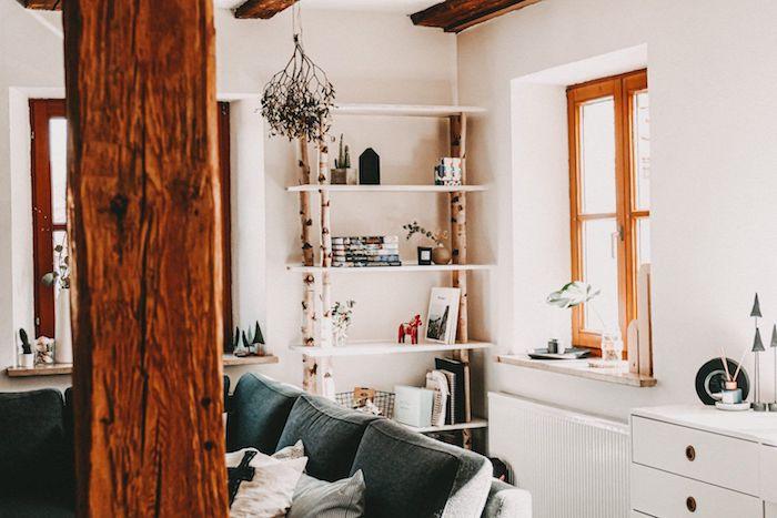 moderne inneneinrichtung birkenstamm deko wohnzimmer regale aus birkenäste großer schwarzer sofa decke mit holzbalken wandfarbe weiß