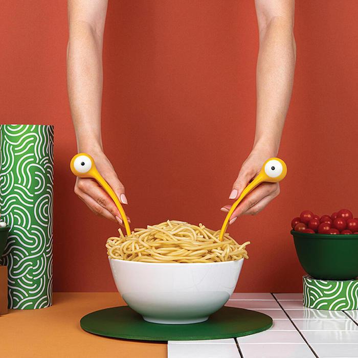 monster pasta eine weiße schüssel mit spaghetti und gelben löffel und gabel mit augen