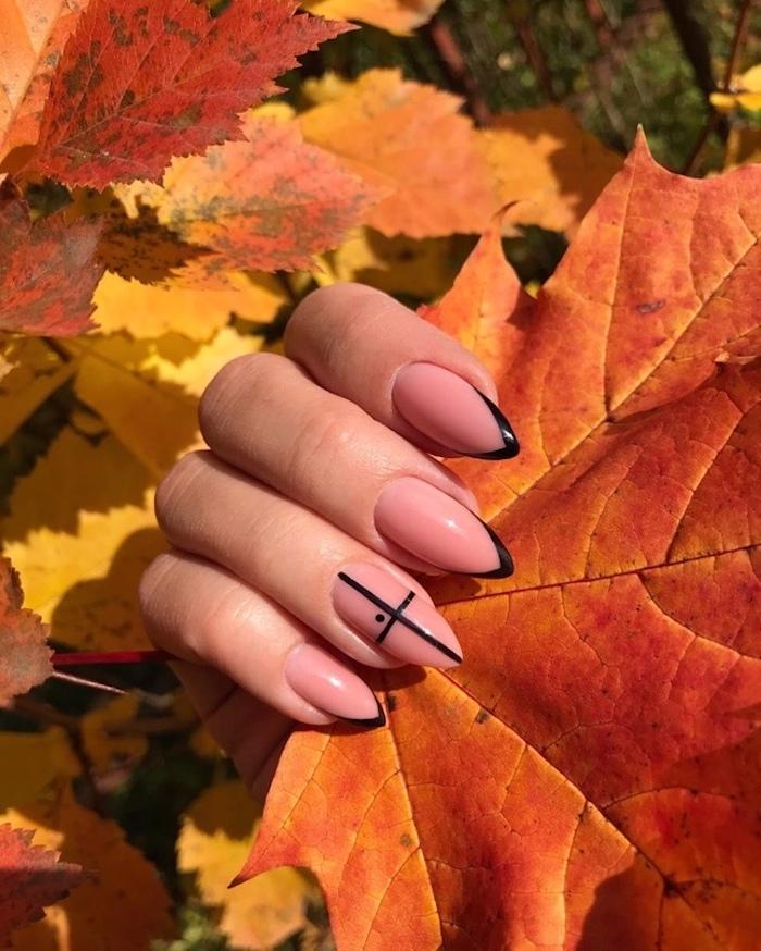 nageldesign für den herbst trends ein pinker nagellack ein kreuz groé orange und gelbe blätter