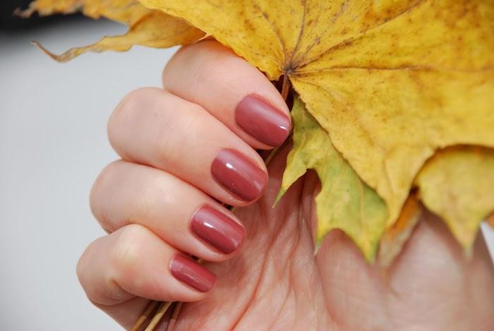 nageldesign herbst eine frau mit hand mit einem großen gelben blatt und einem roten nagellack