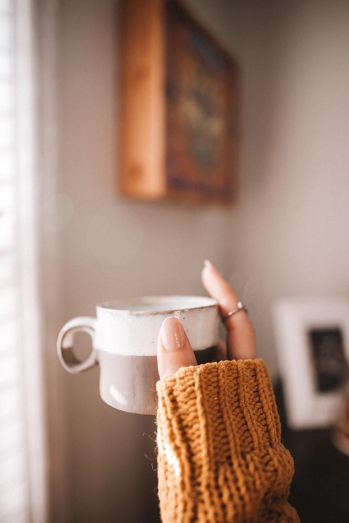nageldesign herbst eine hand einer frau mit ring eine kleine tasse kaffee wand mit bild hand mit beigem nagellack