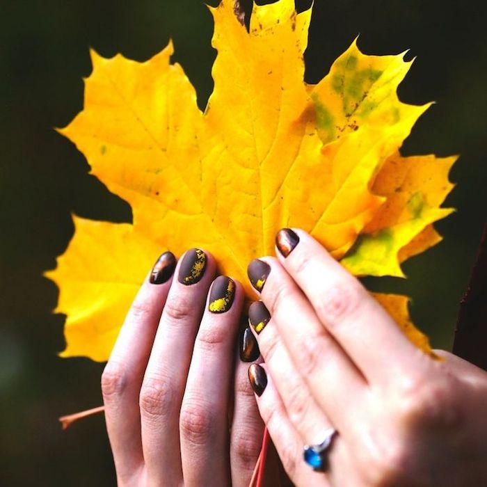 nageldesign herbst hände mit ringen und einem violetten nagellacj zwei große gelbe blätter nagellck für den herbst