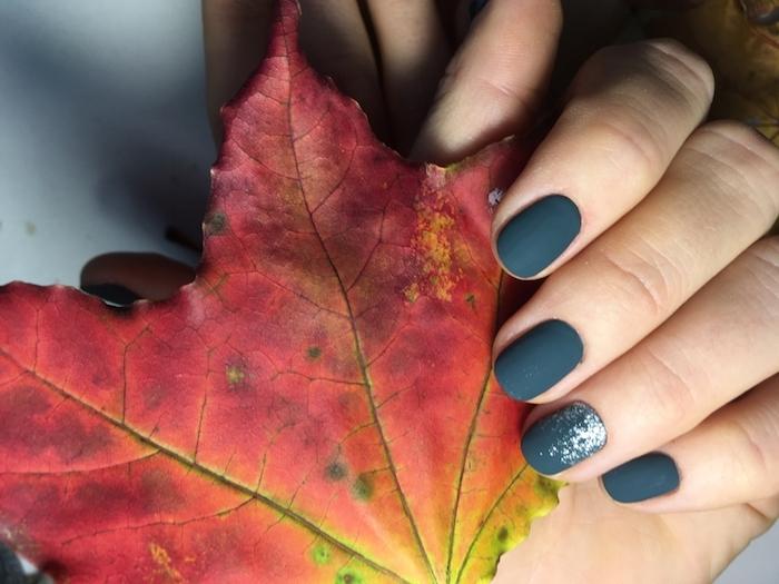 nagellack farben trends herbst eine hand mit dunkelgrünem nagellack und ein herbstblatt eines baumes