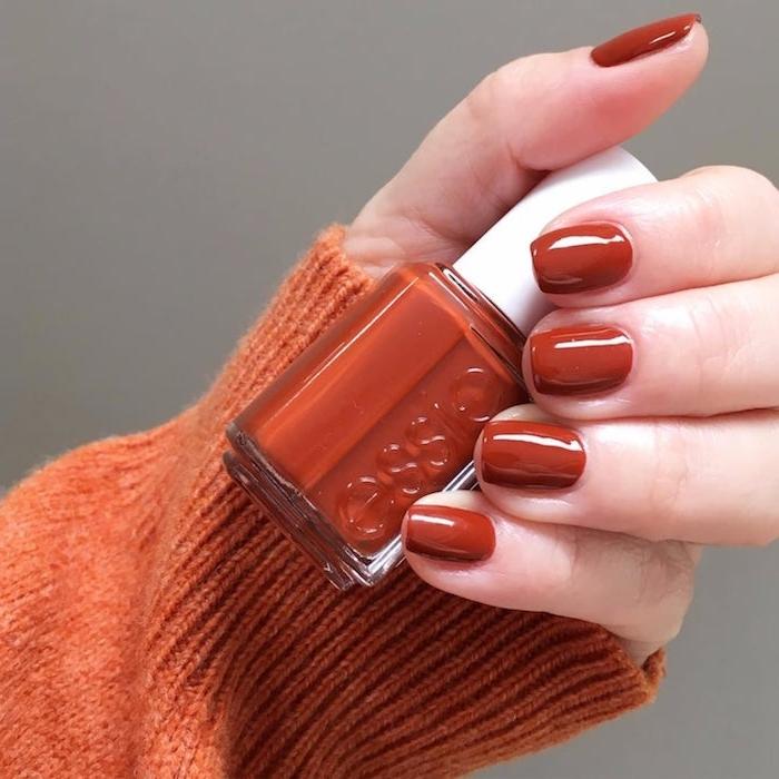 nagellack für den herbst eine frau mit einer kleinen flasche mit dunkelorangem nagellack nageldesign herbst