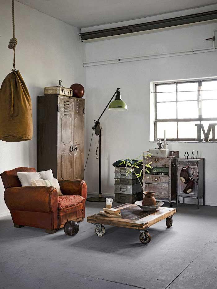 ockerfarbener boxsack roter sessel holztisch mit rädern schränke aus metall industrial style dekoartikel wohnzimmer stilvolle deko inspiration interior design decor trends 2020
