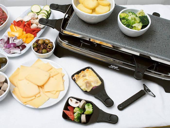 oliven und käse ein tischgrill geschnittene papriaschotten und jartoffeln kleine pfanne für raclette