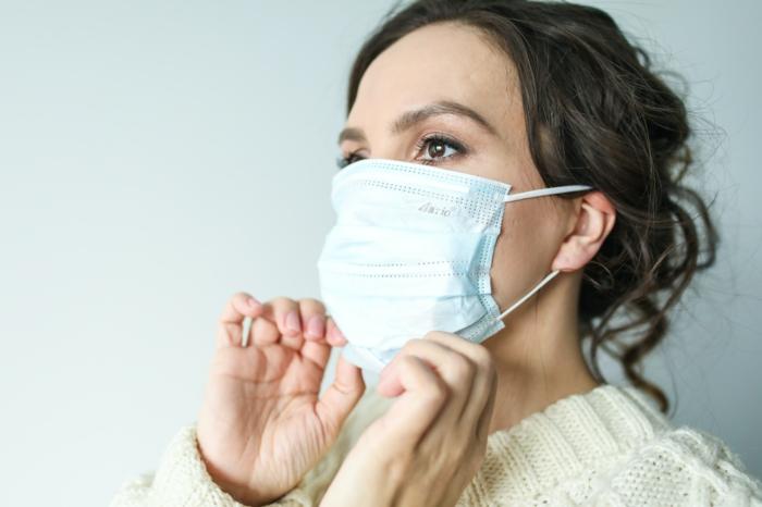 online shoppen in corona zeiten weiße schutzmaske frau mit mundschutzmaske mundschutz
