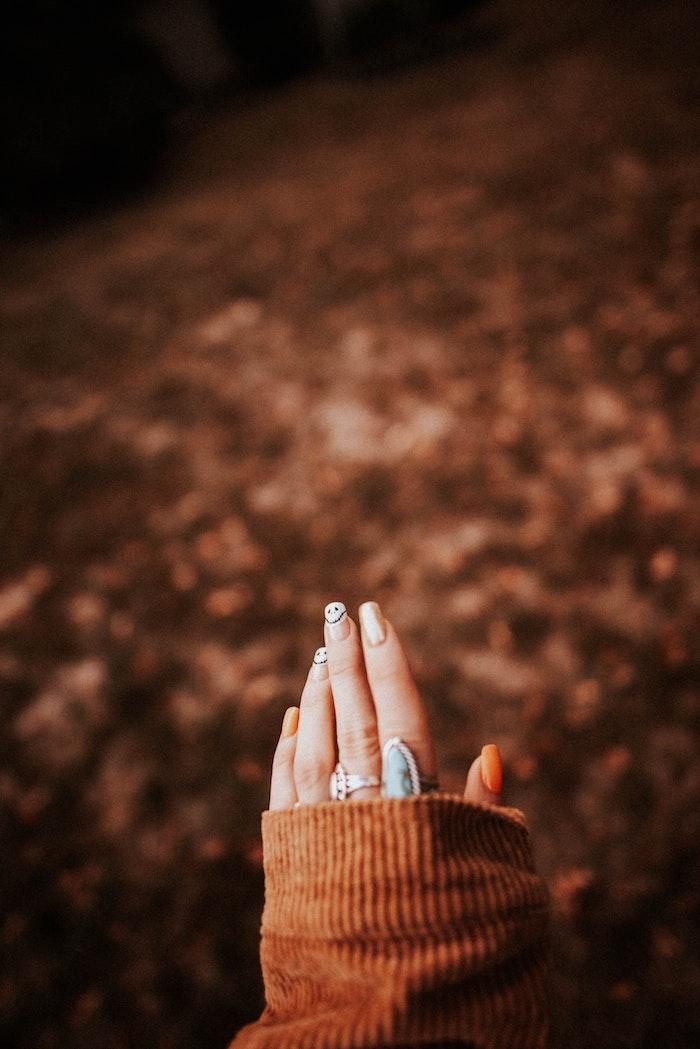 oranger nagellack eine hand einer frau mit zwei blauen großen ringen viele kleine blätter im wald