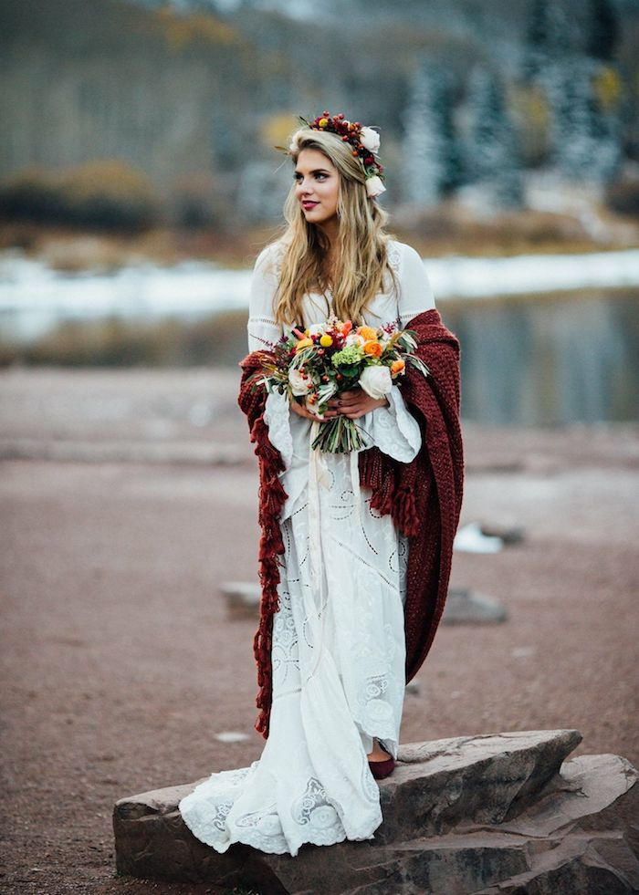 originelle ideen brautkleider 2021 hippie hochzeitskleid winter kleid lange fließende ärmel rote strickjacke bunter blumenstrauß haaraccessoire blumenkranz