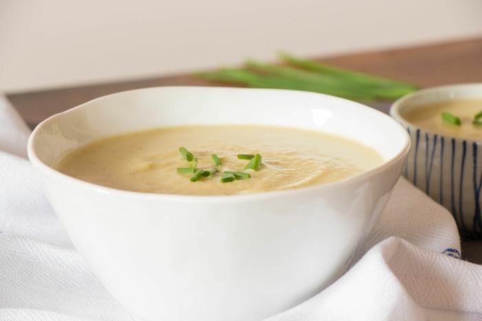 petersilie in einer gelben cremigen kartoffelsuppe eine weiße schüssel mit suppe