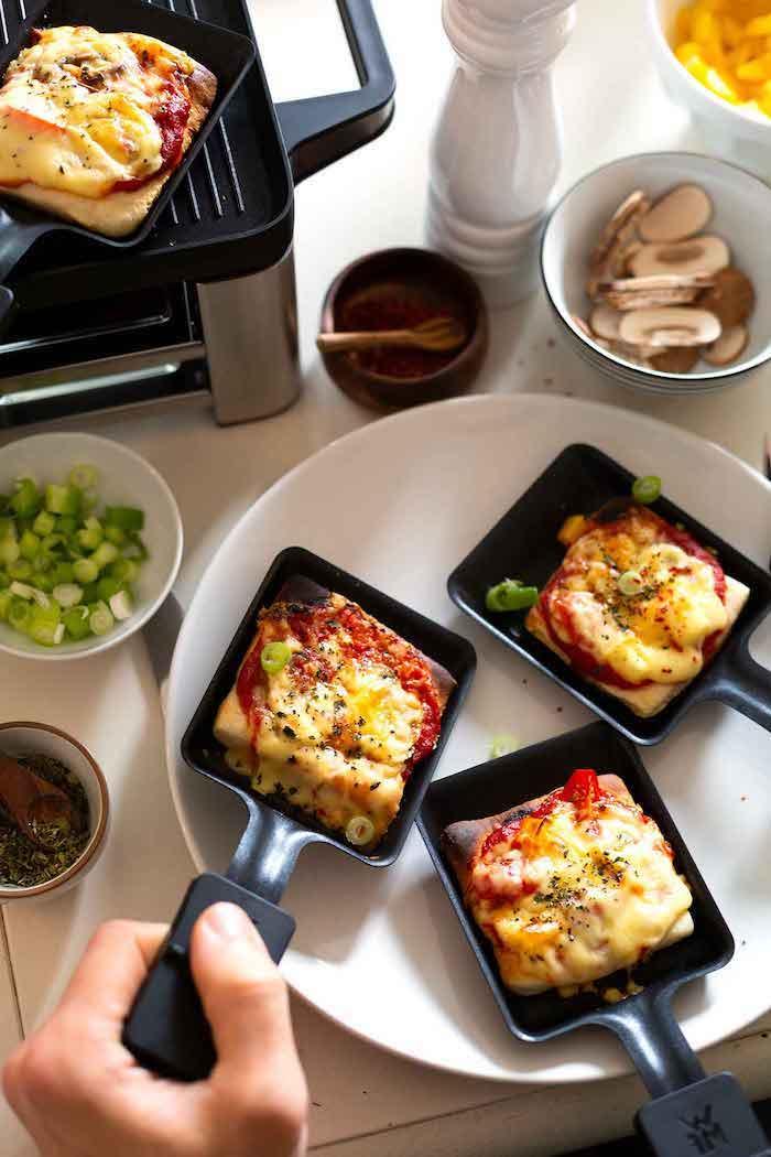 pfänchen für raclette eine hand und pizza rclette zutaten raclette knoblauch käse und champignons