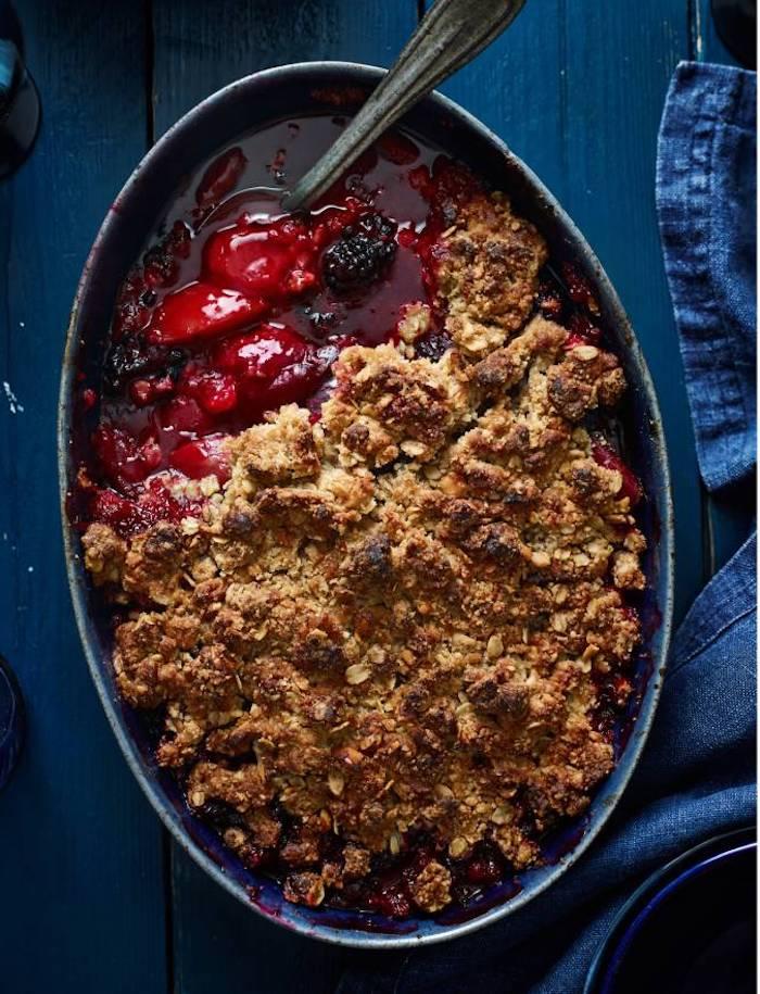 pflaumen crumle ein tisch aus olz ein teller mit crumble mit pflaumen kuchen rezept