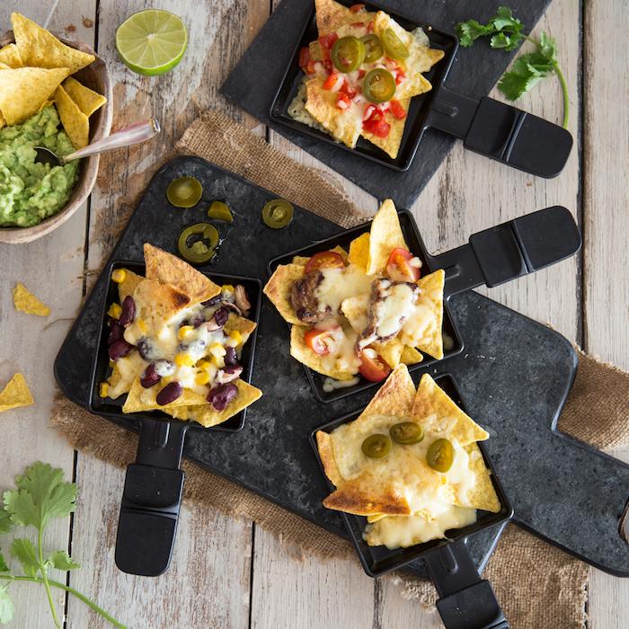 raclette rezepte ein brett mit vielen kleinen schwarzen pfännchen fr raclette raclette zutaten bohnen und oliven raclette käse