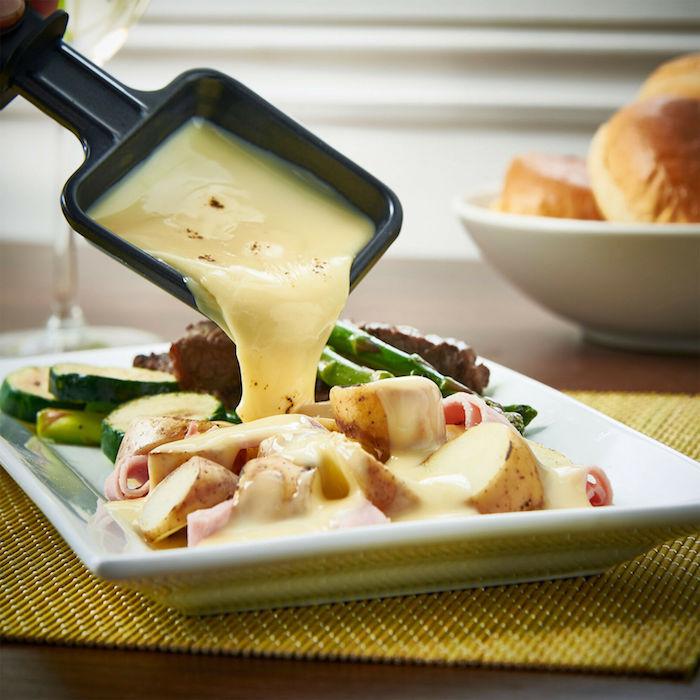 raclette zutaten ein weißer teller mit kartoffeln und spargeln und geschmolzenem käse raclette zutaten eine pfanne mit käse