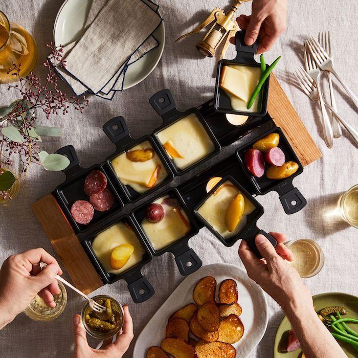raclette zutaten ideen ein holzbrett mit kleinen schwarzen raclette pfännchen mit geschmolzenem käse schinken salami kartoffeln