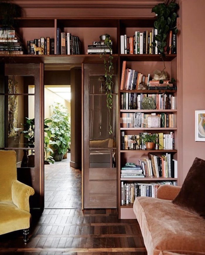 regal mit büchern wandfarbe altrosa gelber sessel vintage wohnung warme farben wohnzimmer ideen modern einrichten grüne pflanze interior design trends 2020 inspo