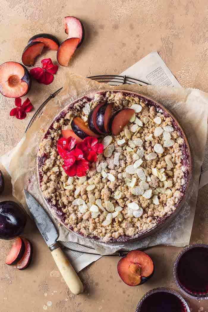 rezept für einen kuchen mit frischen pflaumen ein messer kleine rote blumen glas mit rotem saft pflaumen entkernen