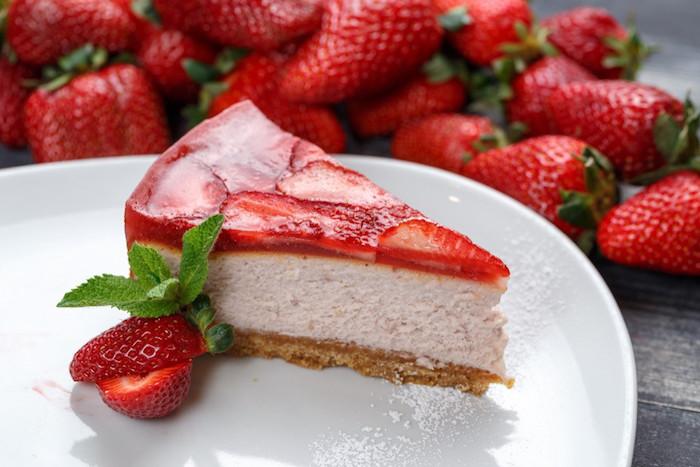 rezept für kuchen mit quark weißer teller mit einem stück kuchen mit roten erdbeeren und frischer pfefferminze viele kleine frische erdeeren