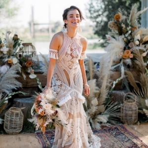 romantisches boho brautkleid neckholder mit quastendetail langes hochzeitskleid spitze blumenmotive schöner blumenstrauß moderne braut inspiration