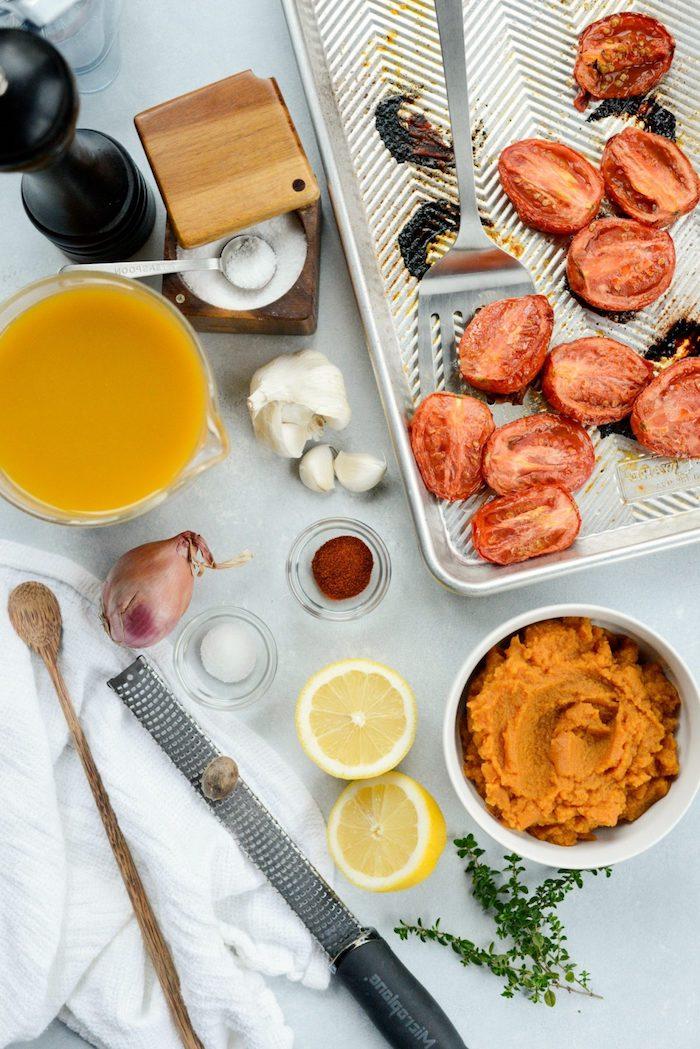 rote tomaten und eine weiße löffel mitpasta aus kürbis geschnittene zitronen und knoblauch zutaten für eine vegane kürbissuppe