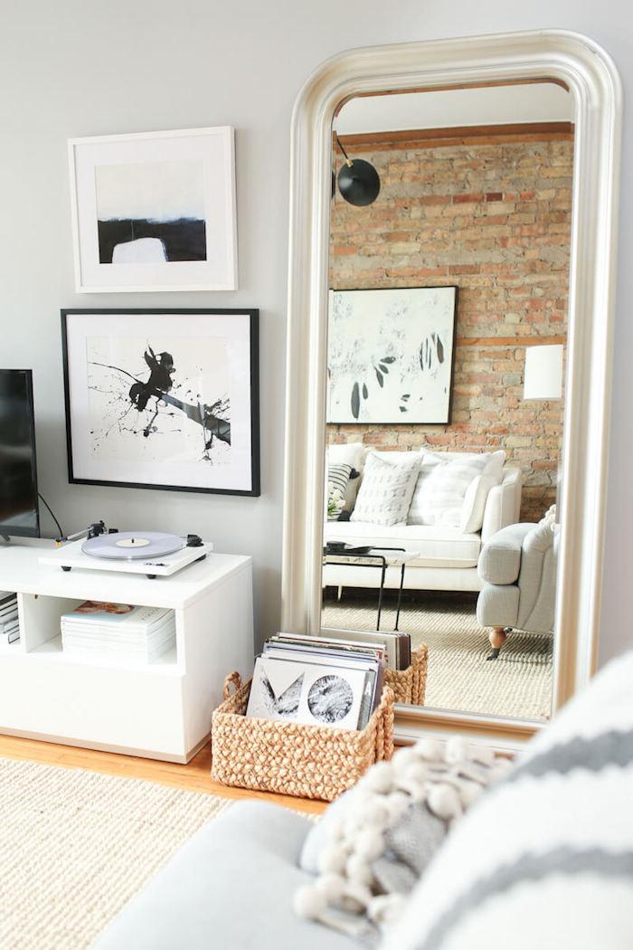 rote ziegelsteinmauer kleinen wohnraum einrichten deko wohnzimmer modern schwarz weiße bildeer an die wand kleiner kasten mit schallplatten weißer couch deko kissen