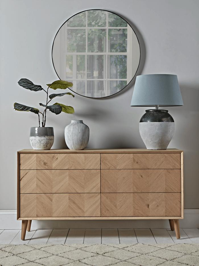 runder spiegel groß scandi style möbel kommode mit schränken aus holz graue tischlampe weißer teppich interior design skandinavisch inspiration kleine pflanze
