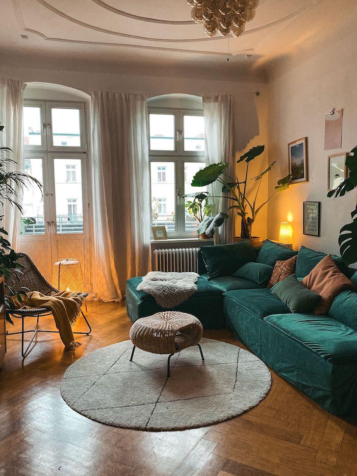 runder teppich und tisch ecksofa smaragdgrün dekorative kissen wohnzimmer gestalten ideen wanddeko inspiration lange weiße gardinen große grüne pflanzen boho chic interior einrichtung