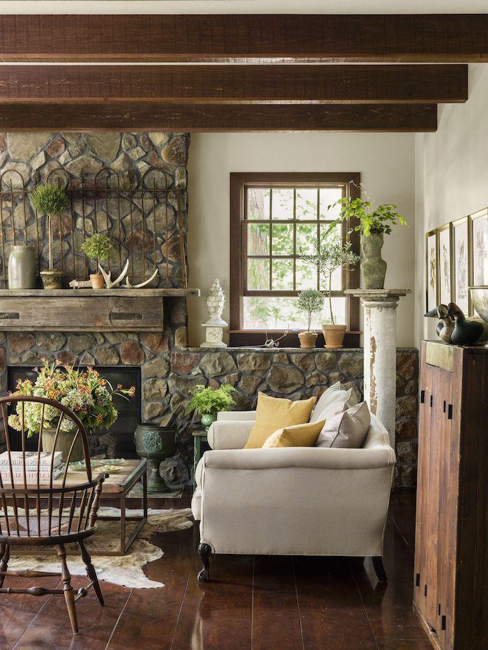rustikaler einrichtungsstil wohnzimmer einrichtungsideen mit kamin weißer sessel boden ais holz viele grüne pflanzen deko gelbe kissen holzbalken bilder an die wand