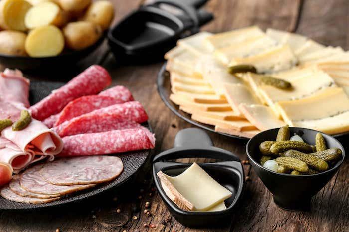 salami und schinken ein kleines schwarzes pfännchen geschnittene kartoffel und gurken käse für raclette