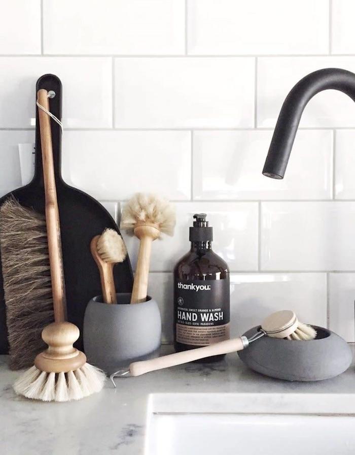 scandi einrichtung küche skandinavische wohnaccessoires spülbürsten aus holz seife in schwarzer flasche weiße fliessen marmor platte schwarzer wasserhahn