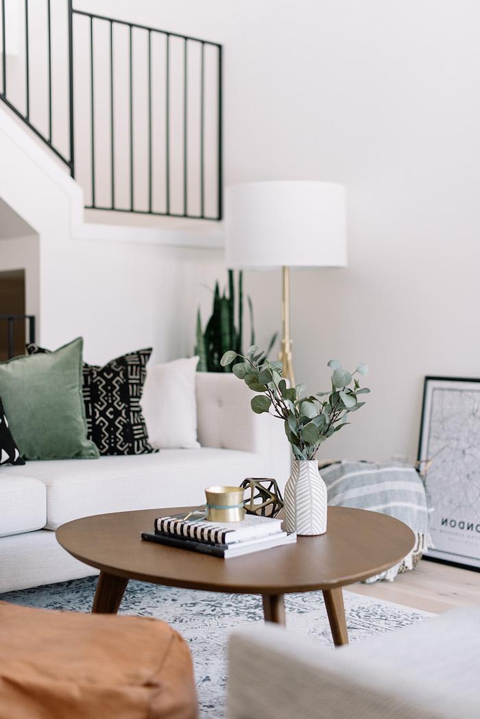 scandi style innenausstatting runder kaffeetisch wohnzimmer einrichten modern weiße vase grüne pflanzen cremefarbener couch schwarze grüne deko kissen skandinavische einrichtung interior design 2020