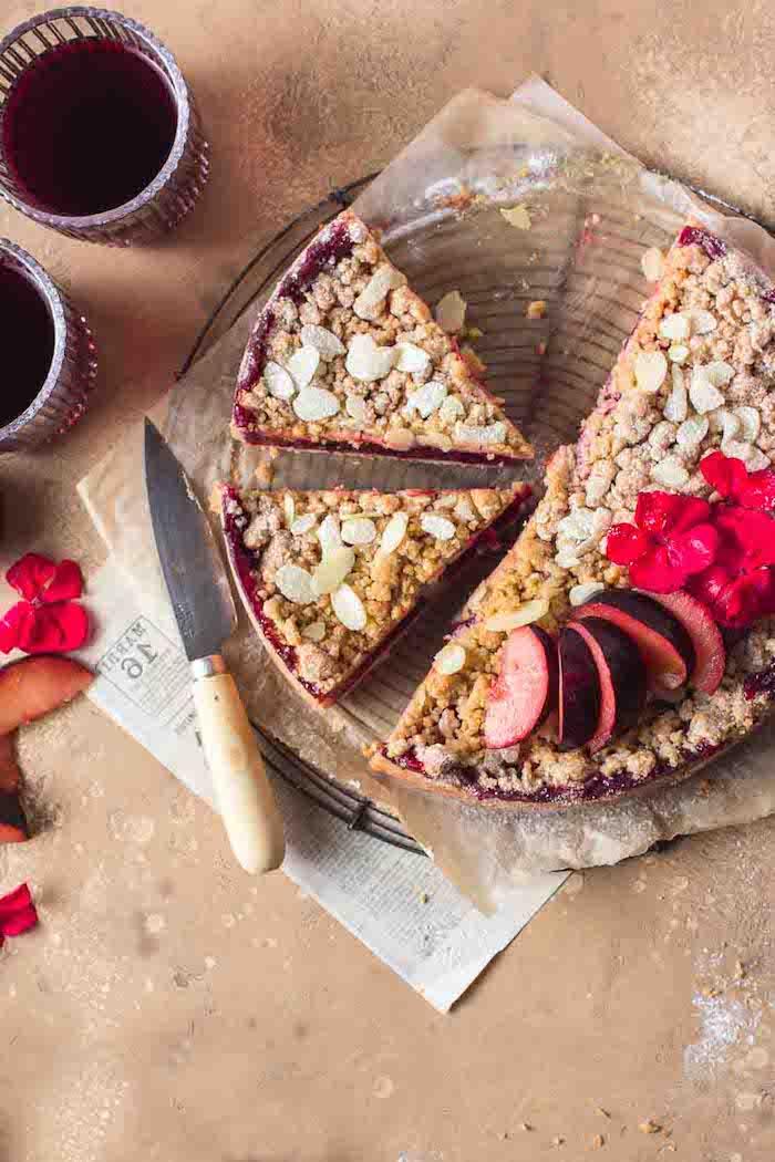 scharfer messer und ein holzbrett und ein kuchen mit pflaumen crumble gläser mit saft