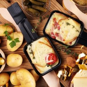 schinkeln grüne oliven kartoffeln und gewürze tomaten und geschmolzener käse im pfännchen für raclette