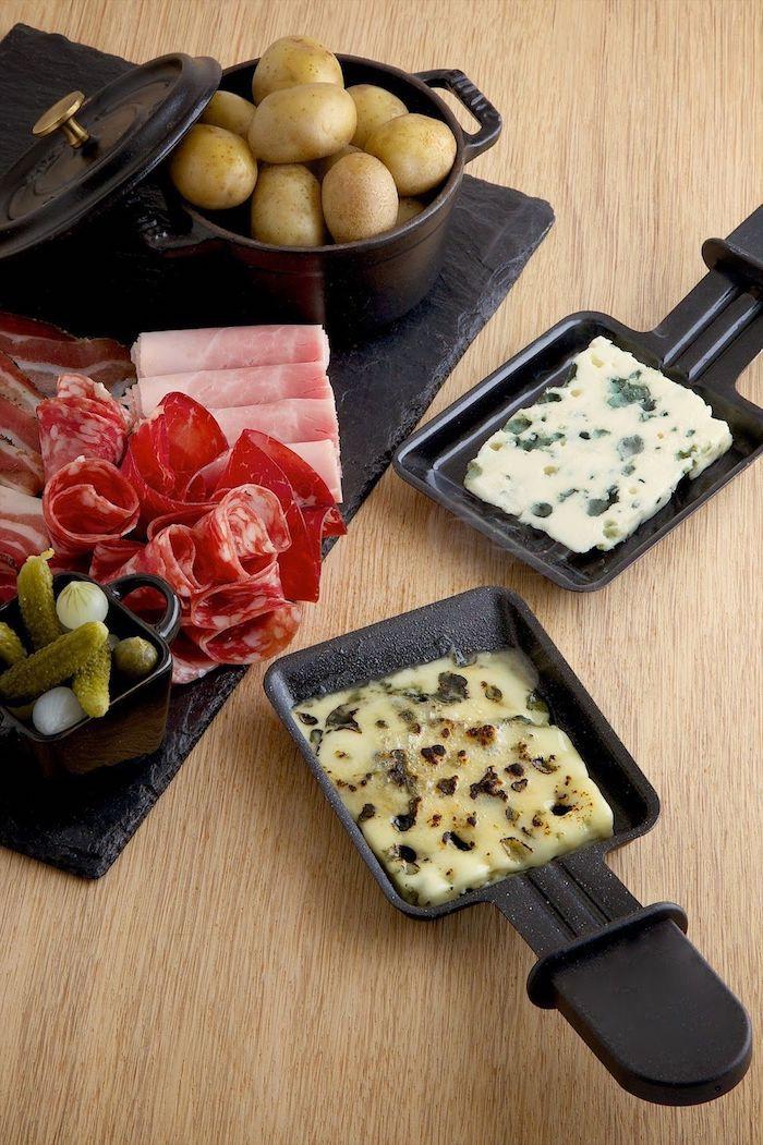schinken und oliven salami die raclette zutaten zwei kleine schwarze üfännchen mit geschmolzenem käse