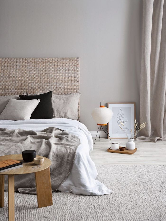 schlafzimmer interior design ideen unaufgehängtes bild linienzeichnung rund dreibeiniger tisch aus holz großes niedriges bett scandic design inspo
