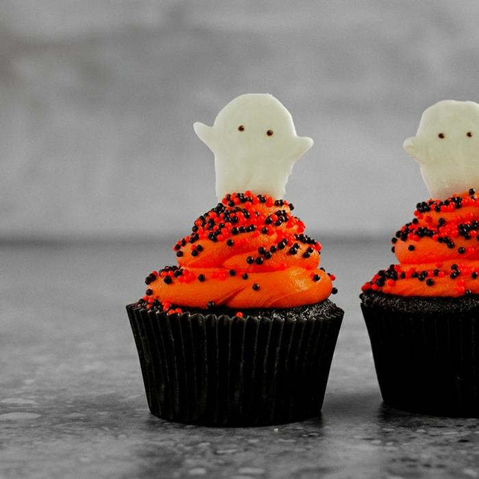 schnelle halloween rezepte schokomuffins mit orangenfarbene buttercreme und geisten und weißer schokoalde