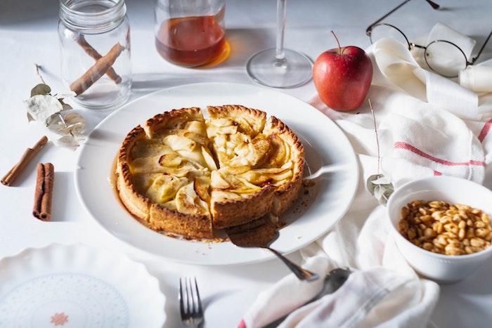 schneller kuchen backen weiße decke und teller mit einem apfelkuchen frische äpflel und glas mit zimt gabel und löffel