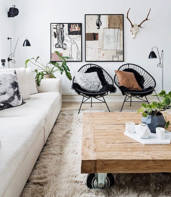 skandinavischer design inneneinrichtung inspiration holztisch mit rädern schwarze stühle weißer couch abstrakte gemälde wanddeko deko wohnzimmer modern interior design minimalistisch