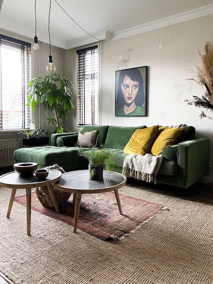 smaragdgrüner ecksofa gemälde von einer frau cremefarbener teppich zwei runde kaffeetische senffarbene kissen boho chic inneneinrichtung interior design inspo