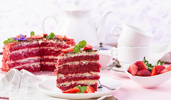 teller mit einem roten kuchen mit quark und mit roten erdneeren und frischer pfefferminze kleine rote geschnittene erdbeere kuchen rezepte einfach und schnell mit wenig zutaten