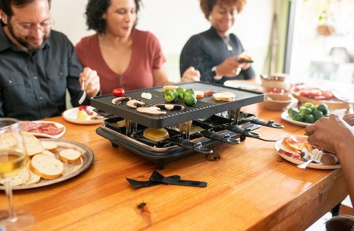 tusch aus holz und ein tischgrill die raclette zutaten käse für raclette glas wein