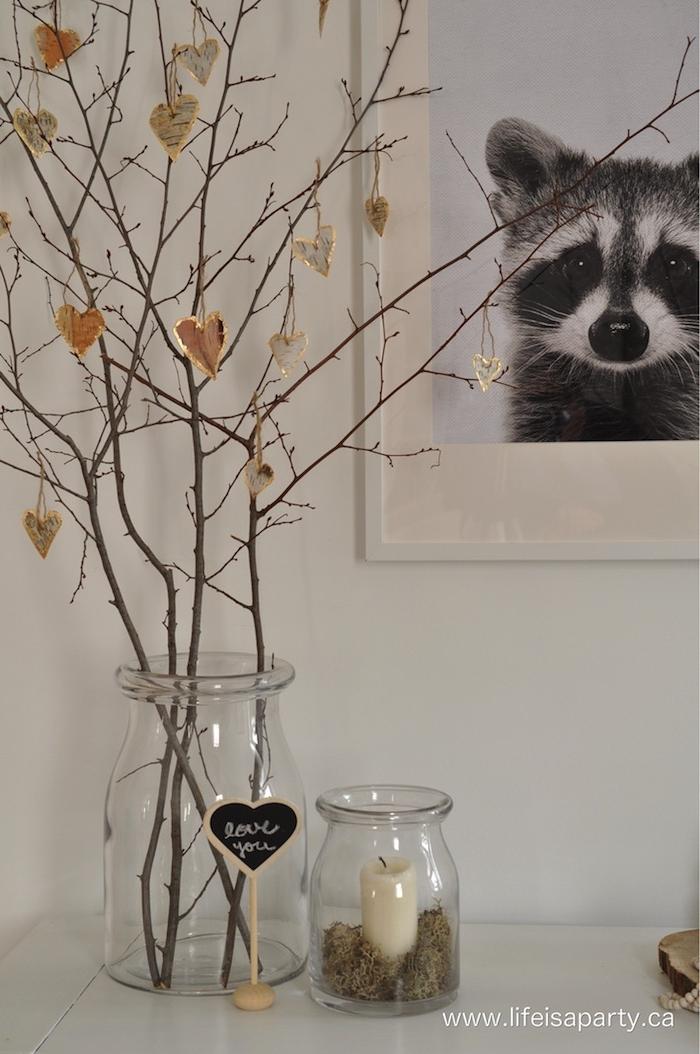 valentinstag dekoration schwarz weißes foto von einem waschbär kleine vase mit weißer kerze birken deko herzen aus birkenstamm aufgehängt auf dünne zweige