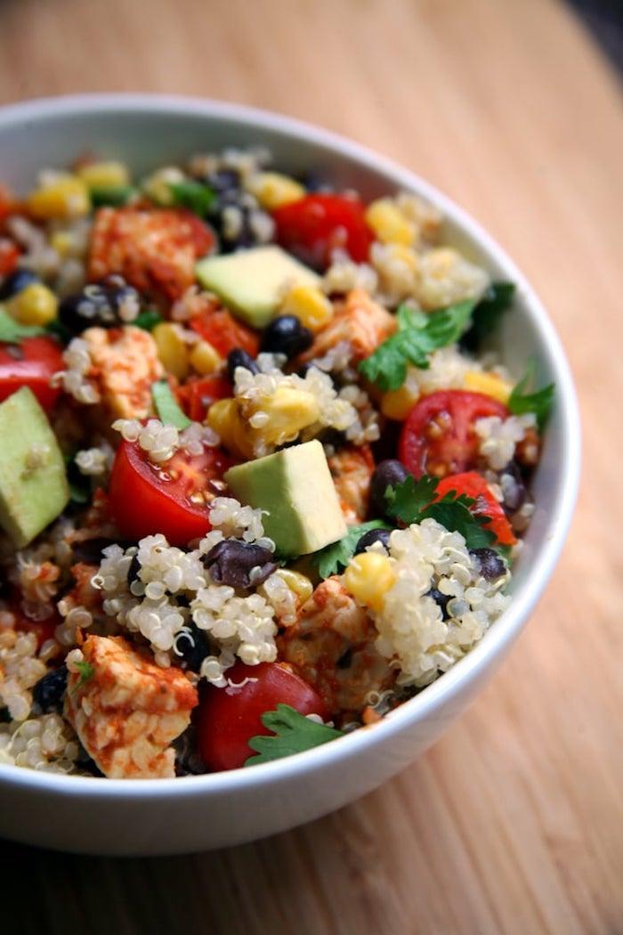 veganer buddah bowl schnelles abendessen salat mit quinoa tomaten avocado petersilie mais schwarze bohnen weiße schüssel gesunde rezepte