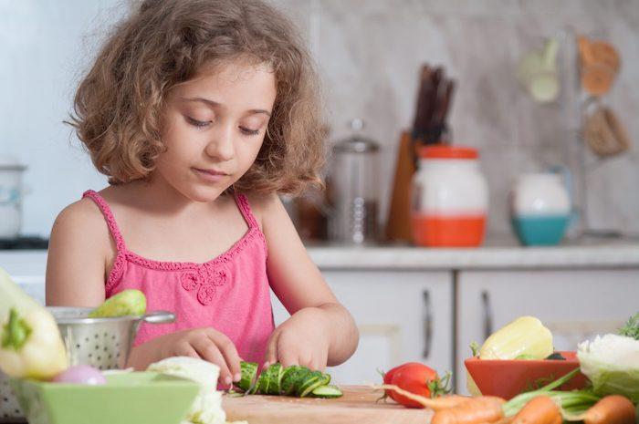 vegetarische speisen für kinder mädchen kocht vegetarisch schneidet gurken