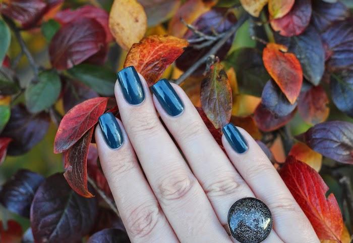 viele kleine rote orange und gelbe blätter im herbst eine hand mit einem großen ring und mit einem dunkelblauen nagellack