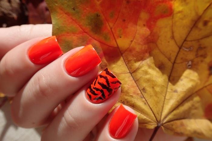 vier finger mit einem orangen nagellack für den herbst ein großes gelbes blatt im herbst